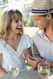 Man placing engagement ring on smiling fiancees finger