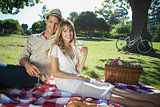 Cute couple drinking white wine on a picnic smiling at camera
