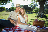 Cute couple drinking white wine on a picnic smiling at each other