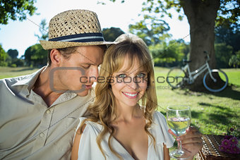Cute couple drinking white wine on a picnic woman smiling at camera