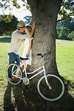 Cute couple leaning against tree in the park