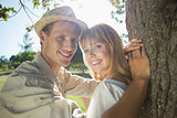 Cute couple leaning against tree in the park smiling at camera