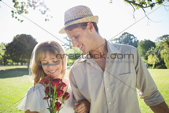 Attractive blonde holding roses standing with partner
