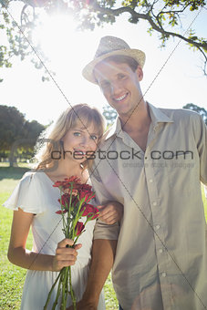 Attractive blonde holding roses standing with partner smiling at camera