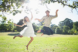 Cute couple jumping in the park together