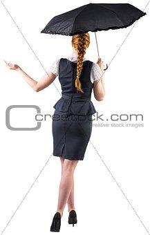 Pretty redhead businesswoman holding umbrella