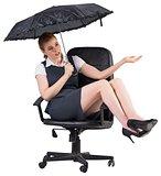 Businesswoman holding umbrella sitting on swivel chair