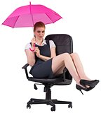 Businesswoman holding umbrella sitting on swivel chair