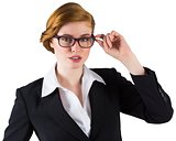 Redhead businesswoman touching her glasses
