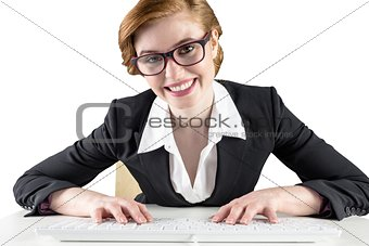 Redhead businesswoman sitting at desk typing