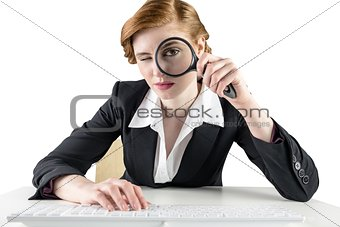 Redhead businesswoman looking through magnifying glass