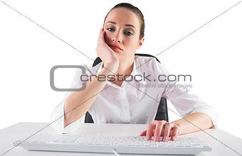 Bored businesswoman typing on keyboard