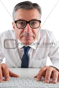 Mature businessman typing on keyboard