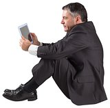 Mature businessman sitting using tablet
