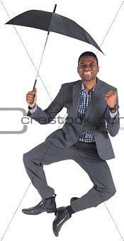 Businessman cheering and holding umbrella
