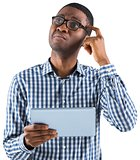 Young businessman thinking and holding tablet
