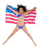 American girl in bikini leaping holding flag