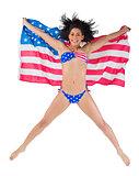 American girl in bikini leaping holding flag
