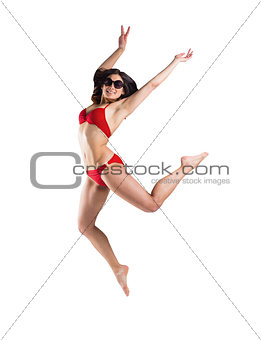Fit girl in red bikini smiling and leaping
