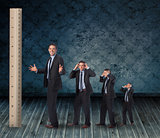 Composite image of multiple image of angry businessman with ruler