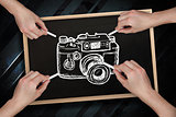Composite image of multiple hands drawing camera with chalk