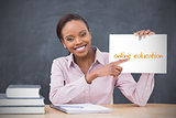Happy teacher holding page showing online education