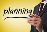 Businessman writing the word planning
