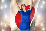 Composite image of cheering football fan in blue jersey holding japan flag