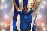 Composite image of cheering football fan in blue jersey holding uruguay flag