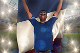 Composite image of cheering football fan in blue jersey holding france flag