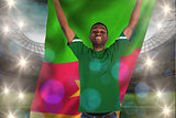 Composite image of cheering football fan in green jersey holding cameroon flag