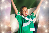 Composite image of cheering football fan in green jersey holding nigeria flag
