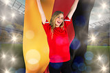 Composite image of cheering football fan in red holding german flag