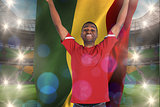 Composite image of excited handsome football fan cheering holding ghana flag