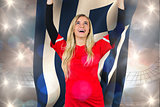 Composite image of cheering football fan in red holding greece flag