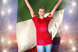 Composite image of cheering football fan in red holding italy flag
