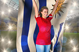 Composite image of cheering football fan in red holding uruguay flag