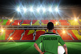 Composite image of cameroon football player holding ball