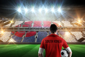 Composite image of south korea football player holding ball
