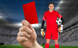 Composite image of hand holding up red card to goalie