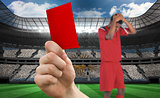 Composite image of hand holding up red card to player