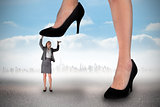 Composite image of businesswoman stepping on tiny businesswoman