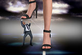 Composite image of female feet in black sandals stepping on businessman