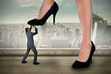 Composite image of businesswoman stepping on tiny businessman