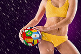 Composite image of fit girl in yellow bikini holding flag football