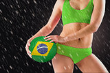 Composite image of fit girl in green bikini holding brasil ball