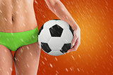 Composite image of fit girl in green bikini holding football