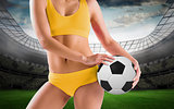 Composite image of fit girl in yellow bikini holding football
