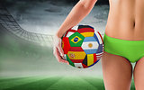 Composite image of fit girl in green bikini holding flag football
