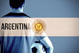 Composite image of argentina football player holding ball